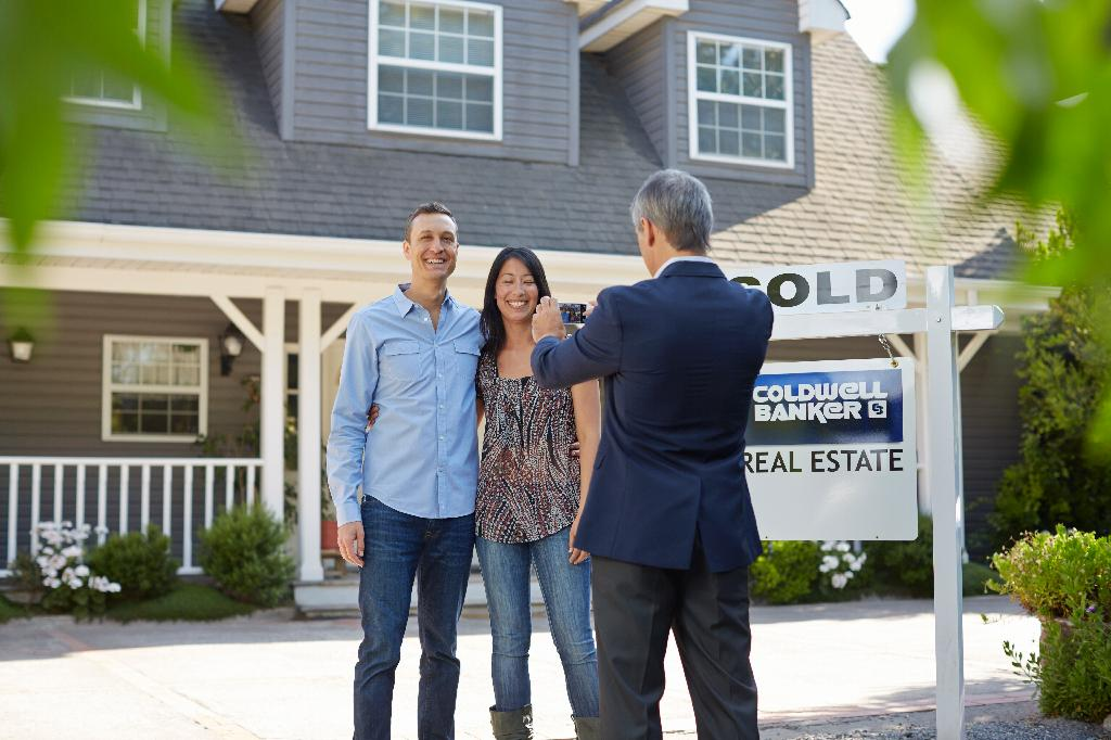 Male Agent Outside Home with New Homeowners and Sold Sign