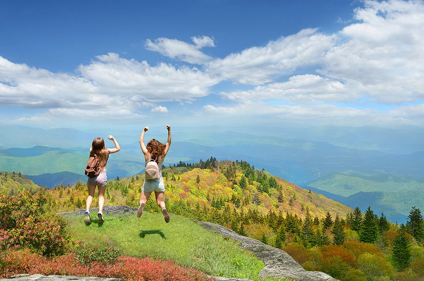 happy-girls-jumping-mountain-overlook